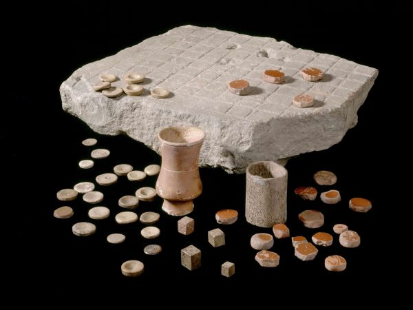 Latrunculi found at Housesteads Roman Fort or Roman Corbridge, complete with pottery counters and dice containers. 2nd-3rd century CE. Corbridge Roman Town and Museum, English Hertitage. Photo: Historic England Archive.