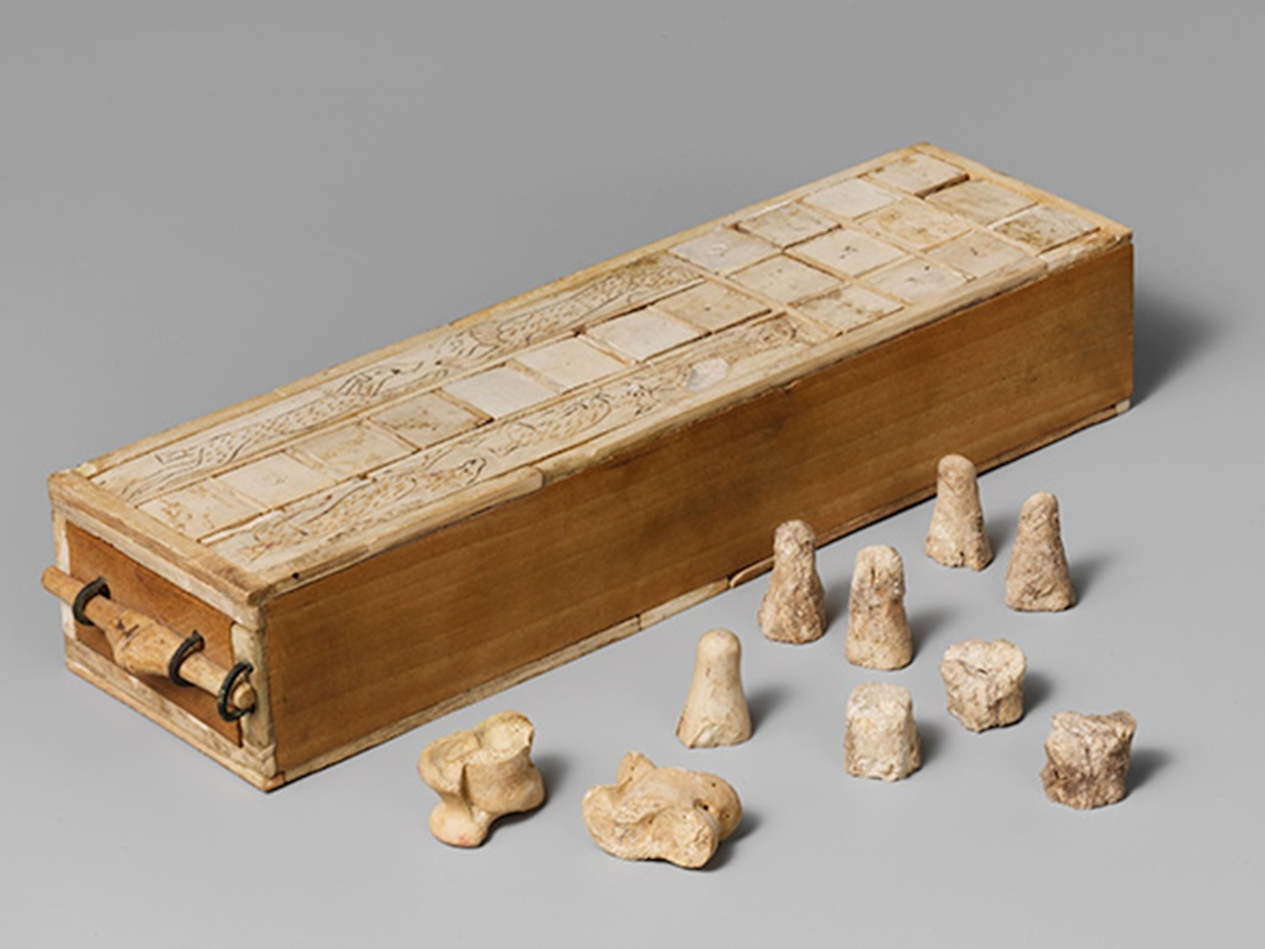 ​Aseb game box with playing pieces and knucklebones dice. 1635–1458 BCE. Egypt, Thebes. Ivory, copper alloy, modern wood. The Metropolitan Museum of Art, New York- 16.10.475a-k