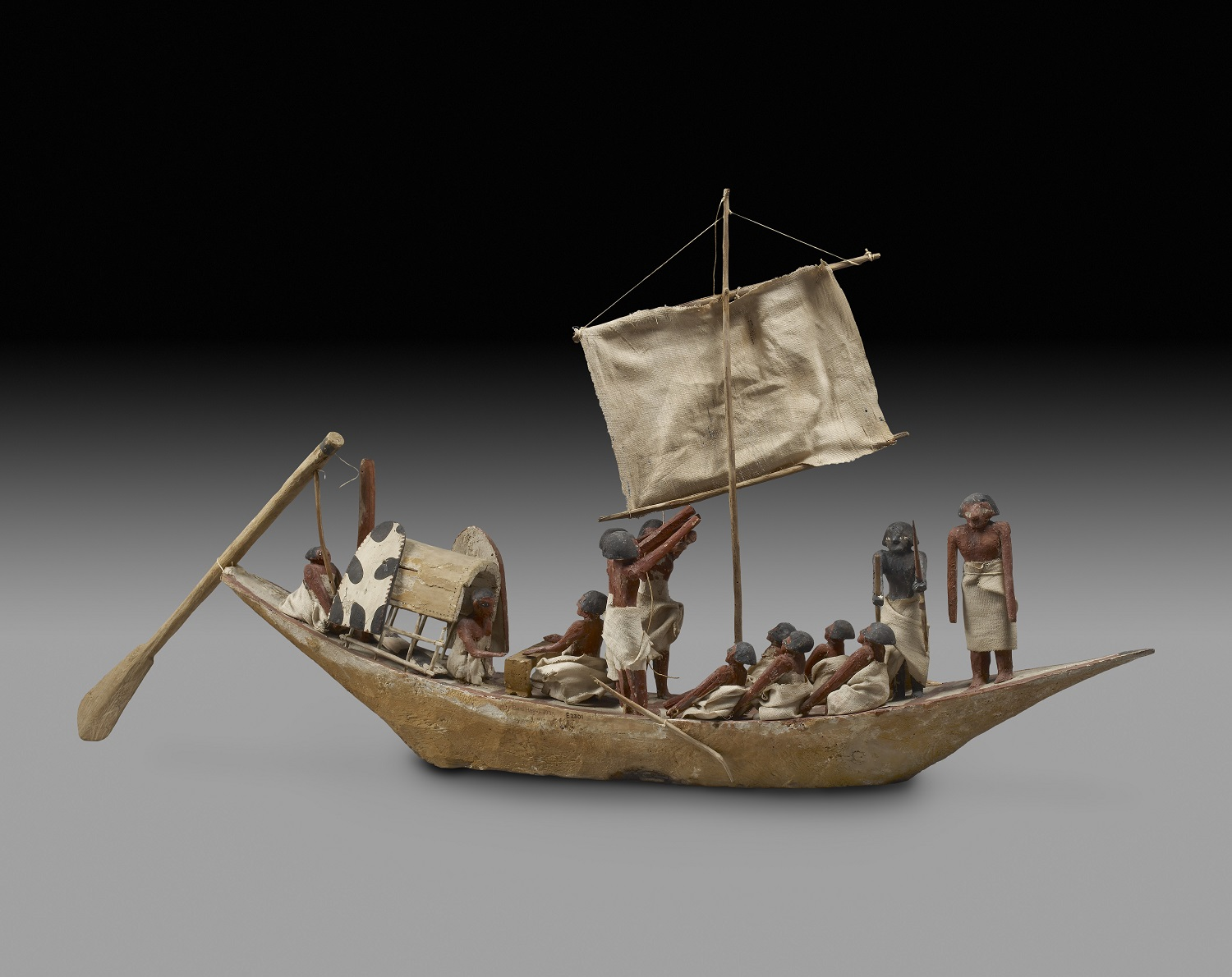 Model of a War Boat. From the Tomb of Nefwa at Beni Hasan, Egypt. IXth - XIth Dynasty (c. 2125 - c. 1940 BC). Note, two sailors are sitting at a table playing the game of Men, which can be indetified by vertical lines going across the gaming board. Ashmolean Museum, E2301.
